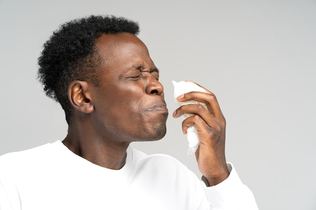Black man blowing nose and sneeze into tissue or napkin, has allergy, first symptoms of cold and flu