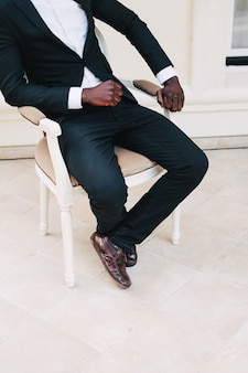 Black man in a business suit sitting in a chair groom black leather.