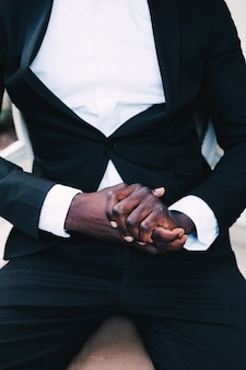 Black man in a business suit sitting in a chair, wedding concept.