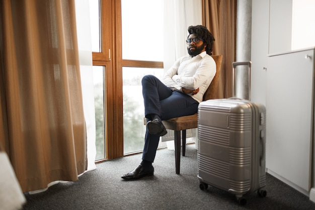 Black man businessman sitting with packed suitcase and looking at window in hotel room