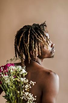 Черный мужчина с букетом цветов на спине