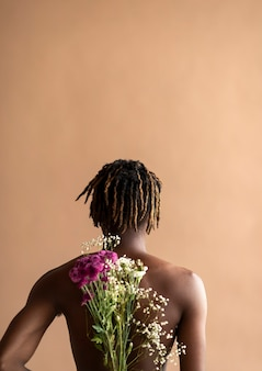 Black man carrying a bouquet of flowers on his back