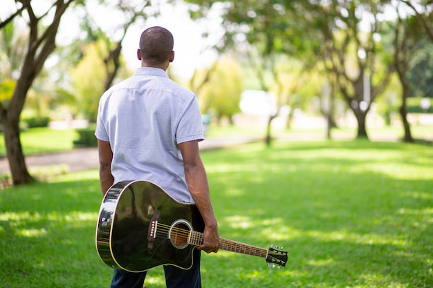 Black man carrying guitar in park