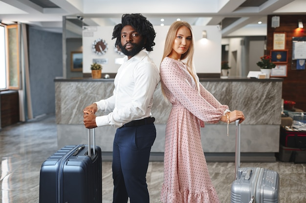 Black man and caucasian woman businesspeople colleagues checking-in in hotel reception desk