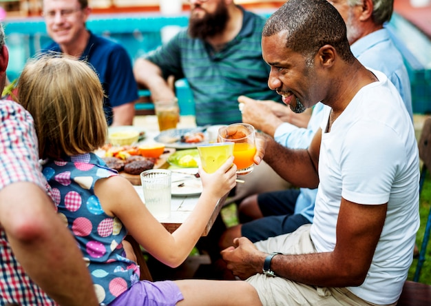 Black man clinking drink with young girl in summer party
