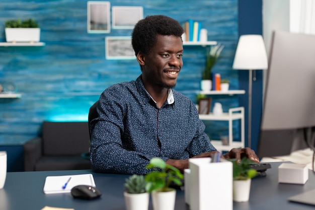 居心地の良い机で自宅で仕事をしている黒人男性のコンピューターユーザー