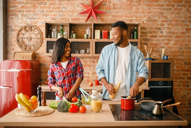 Black man cooking on kitchen, wife drinks coffee