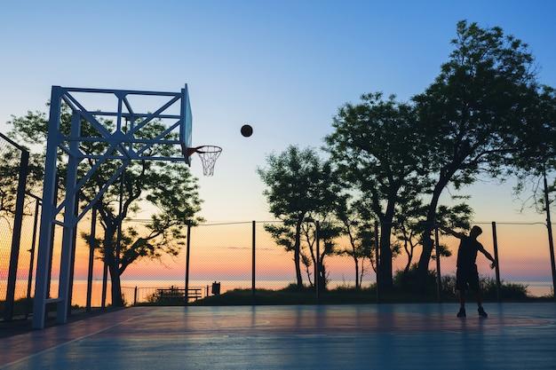 Черный человек занимается спортом, играет в баскетбол на восходе солнца, силуэт