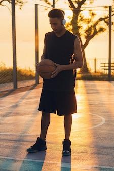 Uomo di colore che fa sport, gioca a basket all'alba, stile di vita attivo, soleggiata mattina d'estate