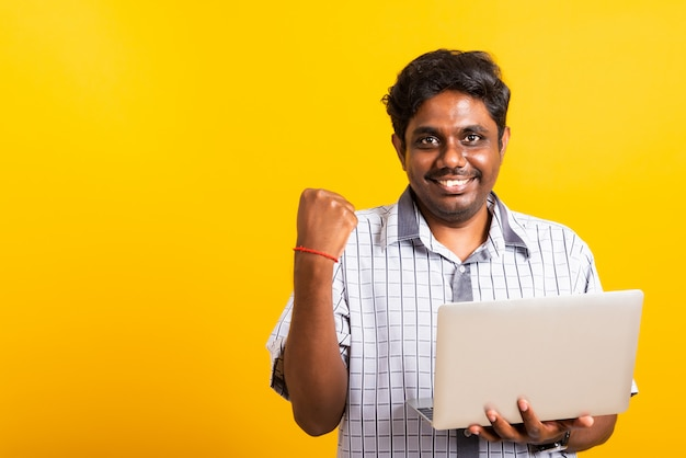 Black man excited holding laptop computer clenching fists and raising a hand for winner