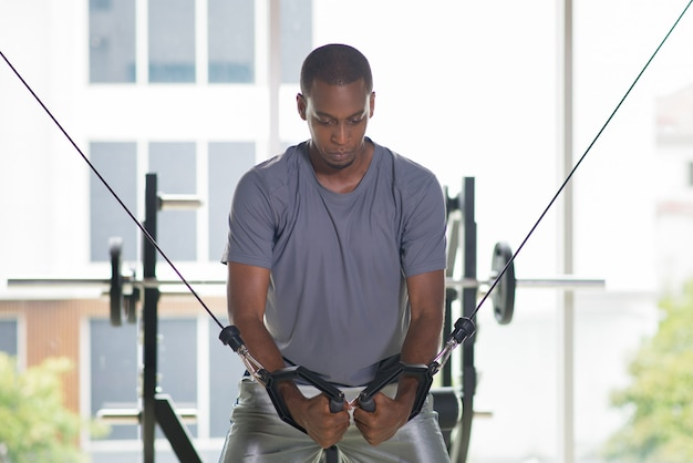 Black man exercising pecs on gym equipment