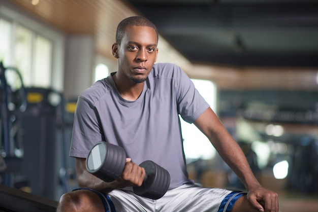 Black man exercising with dumbbell and looking at camera