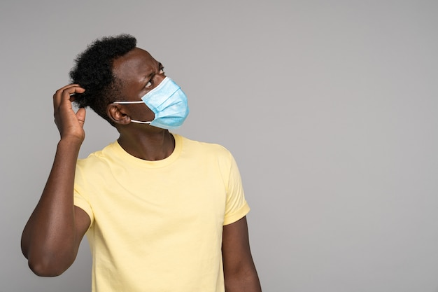 Black man in face mask scratches head thinks looking up