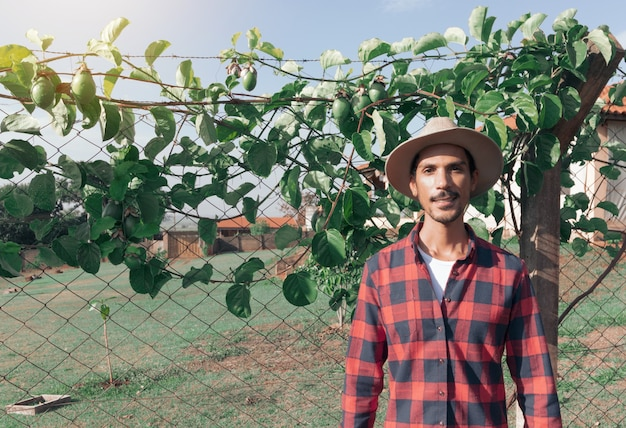 Black man farmer in hat on farm, passion fruit plant in background. space for text.