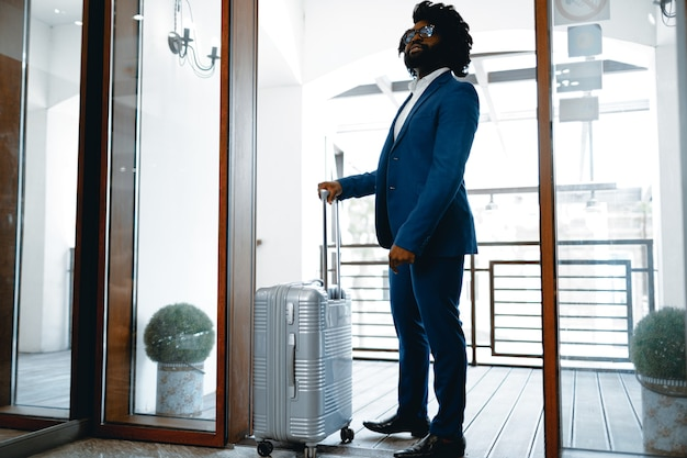 Black man in formal suit with packed suitcase entering hotel door.