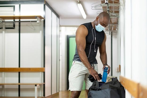 체육관 라커룸에서 준비하는 흑인. 그는 의료용 마스크를 쓰고 있다. 뉴노멀 컨셉.