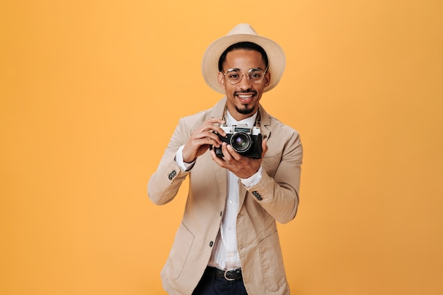 Black man in hat and glasses holding retro camera on isolated wall