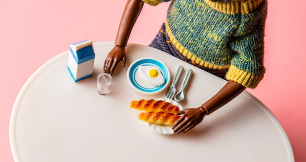 Black man have a breakfast with eggs, milk and buns on a table.