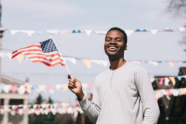 Черный человек держит американский флаг и смеется