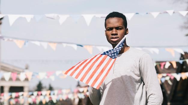 Черный человек держит американский флаг и смотрит на камеру