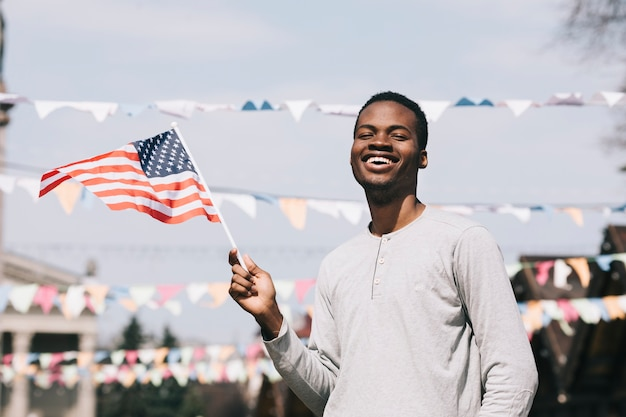 Black man holding american flag and laughing