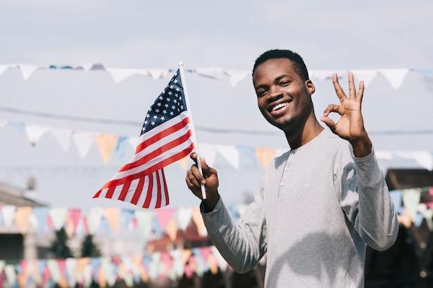 Uomo nero che tiene bandiera americana e che guarda l'obbiettivo con gesto ok