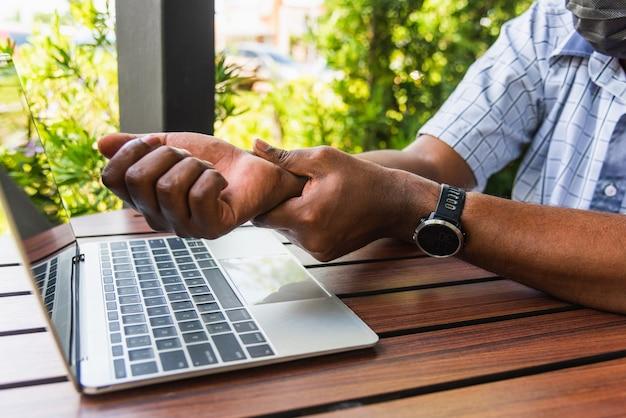 Черный мужчина держит его боль в запястье от использования портативного компьютера