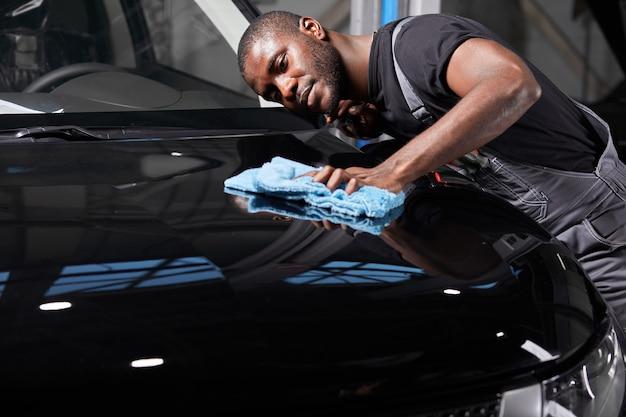黒人男性はマイクロファイバーを手に持って、自動車サービスで車を磨きます