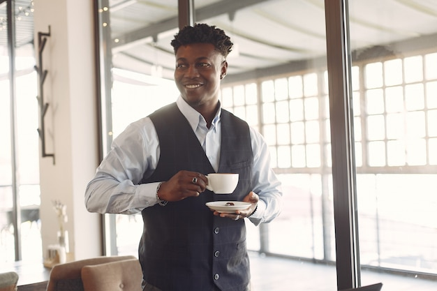 Черный человек в синей рубашке стоит в кафе