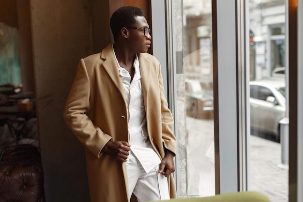 Черный человек в коричневом пальто стоит у окна