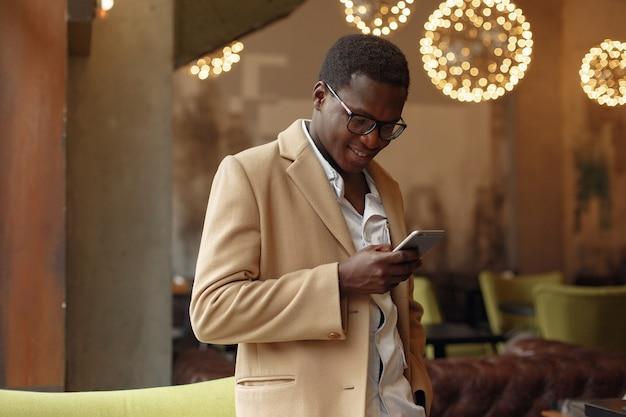 Черный человек в коричневом пальто стоит с мобильным телефоном