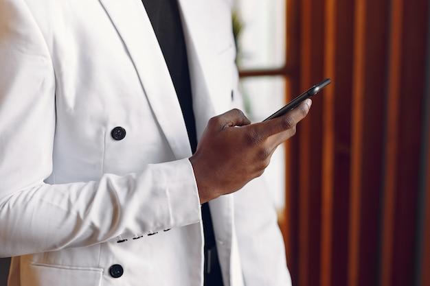 電話で立っている白いジャケットの黒人男性