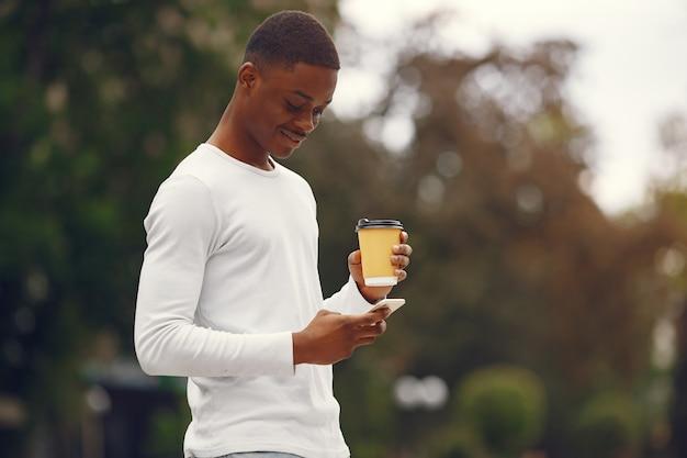 여름 도시에 흰색 스웨터에 흑인 남자