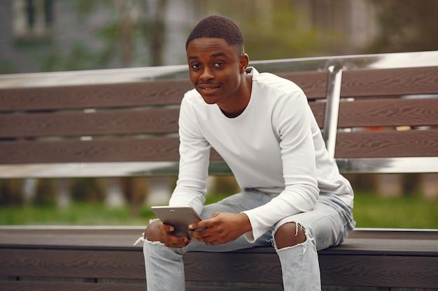 Черный мужчина в белом свитере в летнем городе