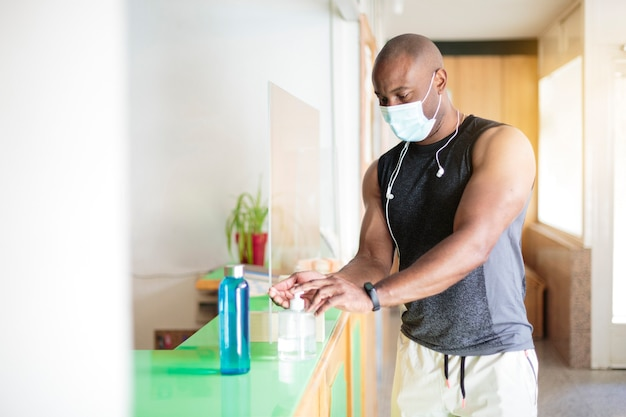 Черный мужчина в спортивной одежде и маске распыляет дезинфицирующий гель на руки. он входит в спортзал.