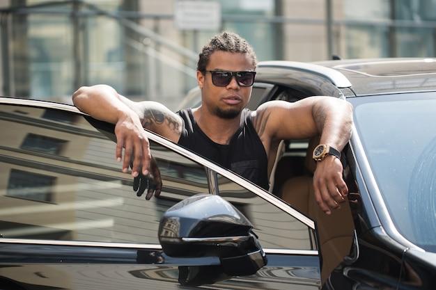 Черный мужчина в солнцезащитных очках стоит возле автомобиля с современным зданием на фоне