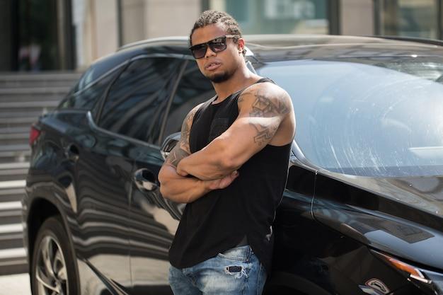 Черный человек в темных очках стоит возле машины
