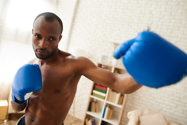 Black man is boxing in sporty gloves at home.