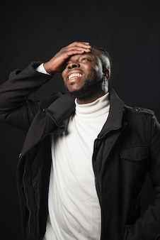 Black man laughing with his hand on his face. mid shot. black background.