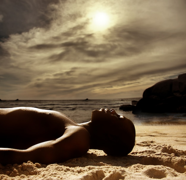 Black man laying on the beach