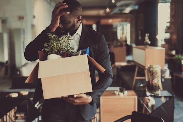 Черный человек покидает рабочее место с офисной коробкой.