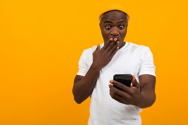 Black man looks in surprise on the phone on an orange background