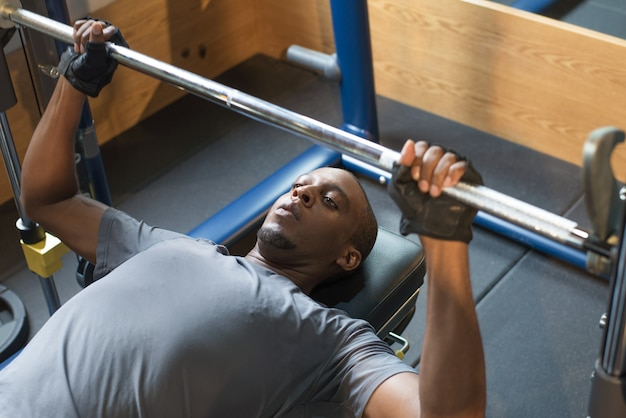 Black man lying and lifting barbell in gym