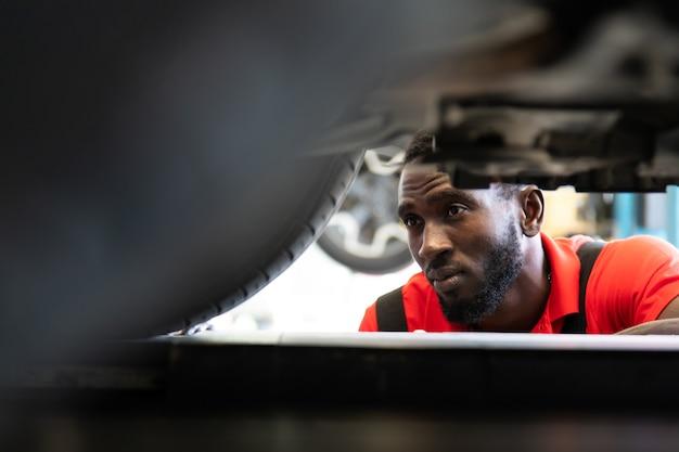 자동차 정비소에서 차량 아래에서 일하는 흑인 정비사. 자동차 수리 차고에서 일하는 전문 정비사.