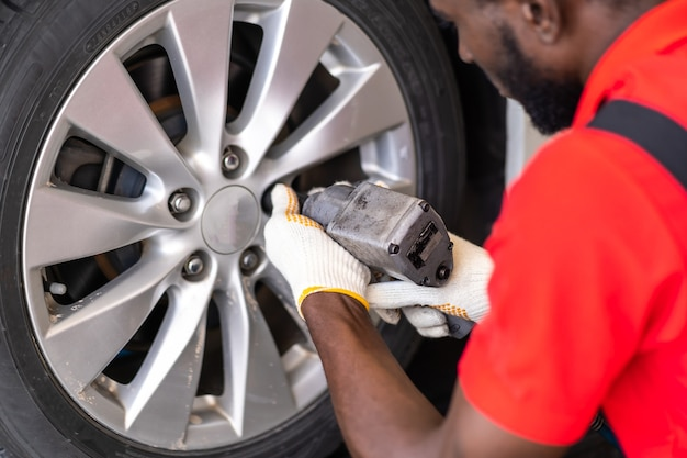 Black man mechanic working under a vehicle in a car service station