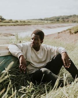 Чернокожий мужчина снимает уличную одежду у воды