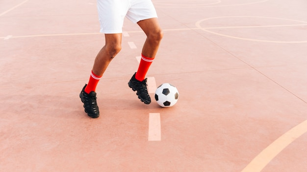 Uomo di colore che gioca a calcio allo stadio