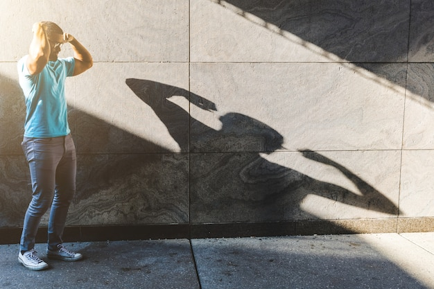 Black man playing with his shadow on the wall