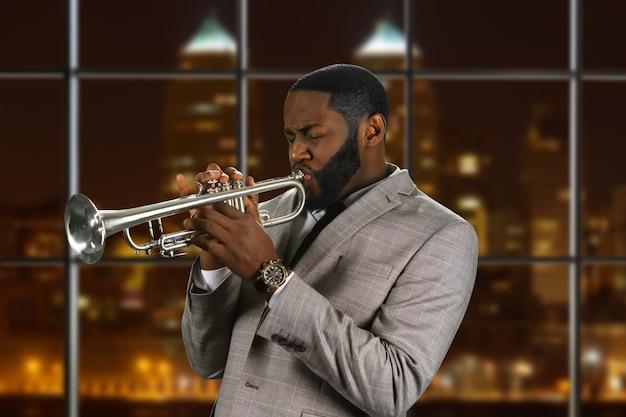 Черный мужчина играет на трубе.
