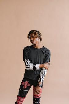 Black man posing by a beige background